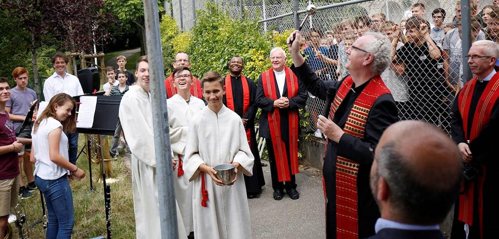 Pater Alexander Holzbach segnet das neue Wegschild
