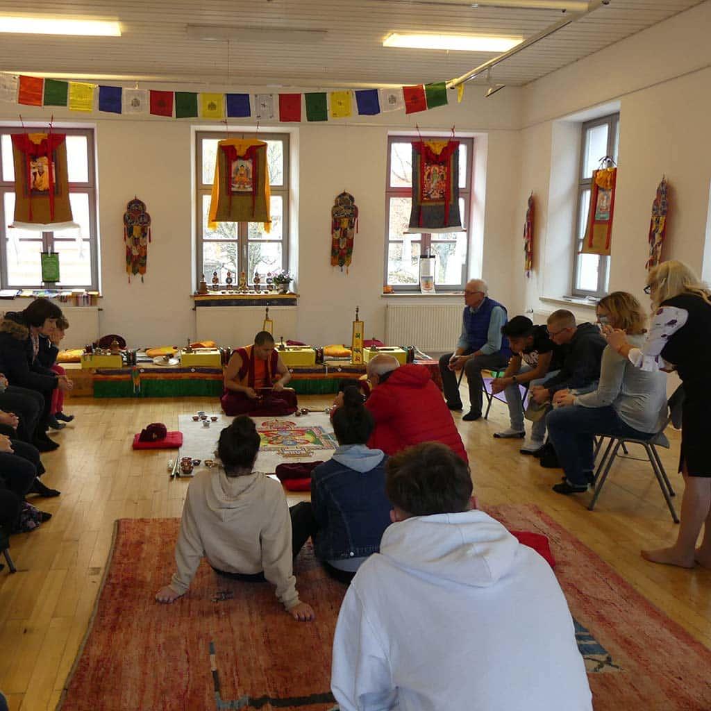 Gäste bestaunen die kunstvolle Arbeit tibetischer Mönche in Friedberg (Bayern)