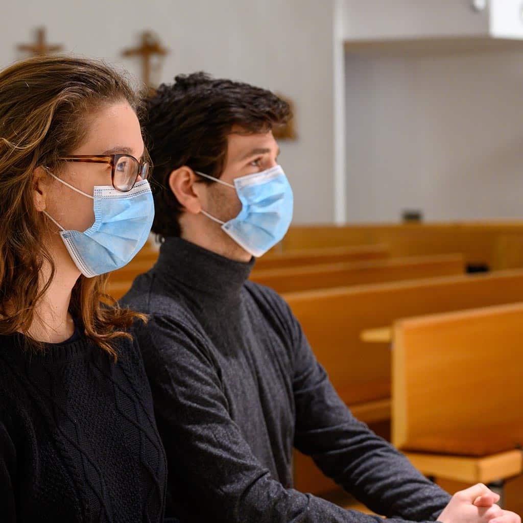 Paar mit Mundschutz in einer leeren Kirche
